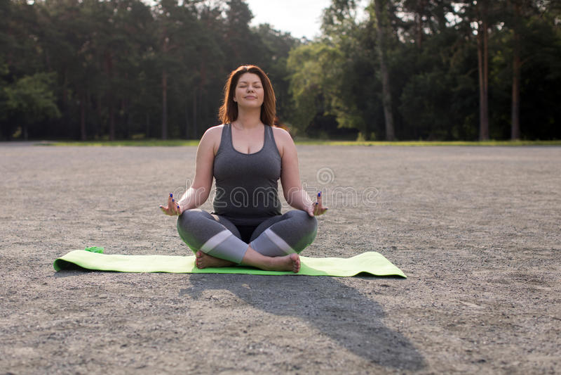 Menina positiva do tamanho que medita fora a ioga imagem de stock royalty free