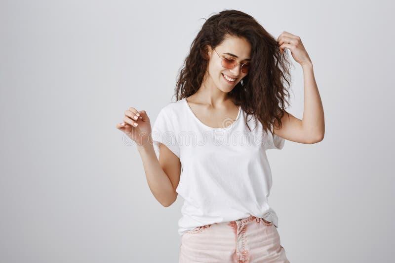 A menina positiva e brilhante aprecia cada momento Retrato da mulher delgada atrativa à moda em óculos de sol na moda, levantando fotografia de stock royalty free
