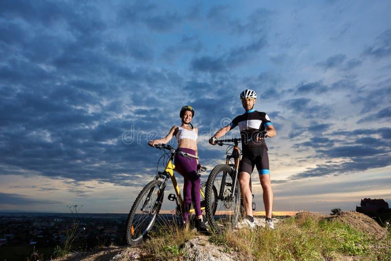 Menina positiva e homem que levantam com as bicicletas nos capacetes e no sportswear fotografia de stock royalty free