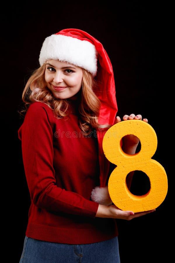Menina positiva em um traje de Santa do Natal que guarda um número oito em um fundo preto conceito 2018 imagem de stock