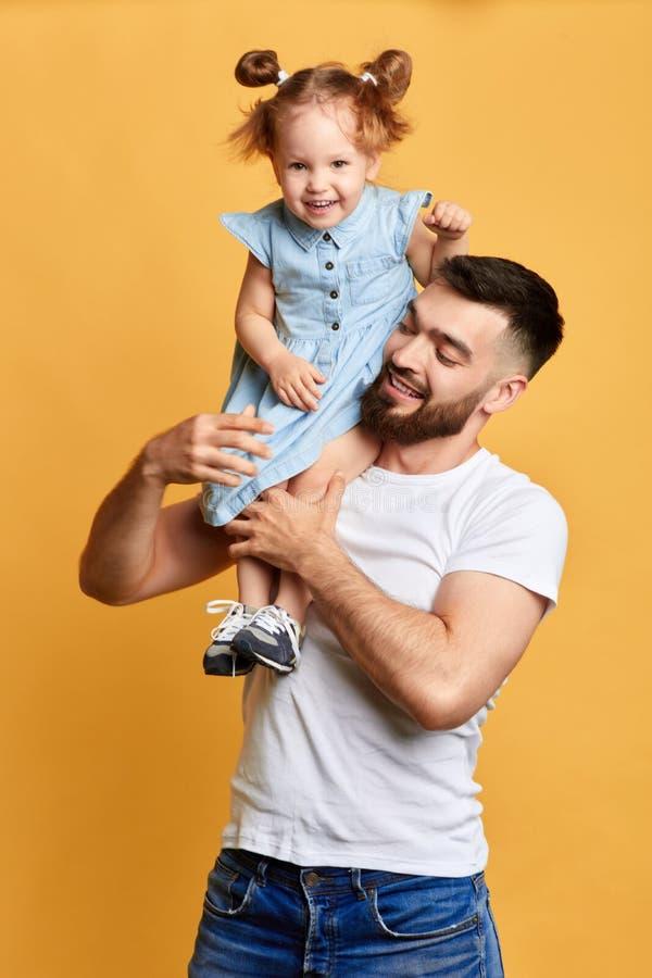 Menina positiva pequena bonito que senta-se no ombro e no riso do pai foto de stock royalty free