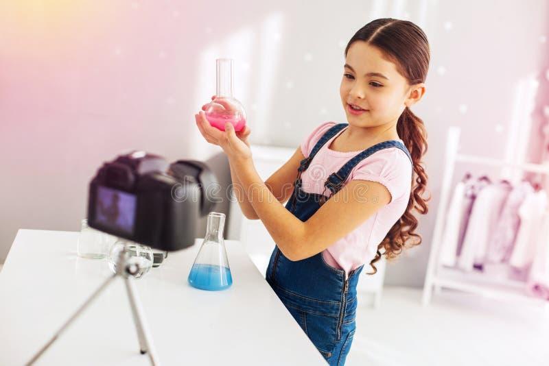 Menina pré-escolar afeiçoada da química que filma extremamente o blogue sobre sua experiência fotos de stock royalty free