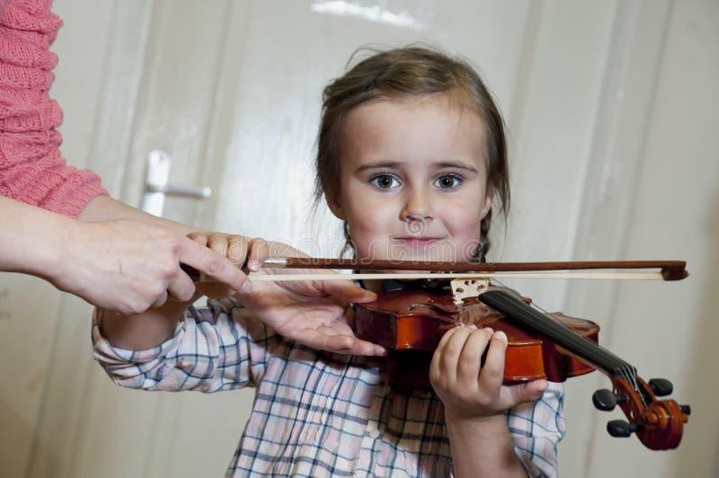Menina pré-escolar bonito que aprende o jogo do violino foto de stock