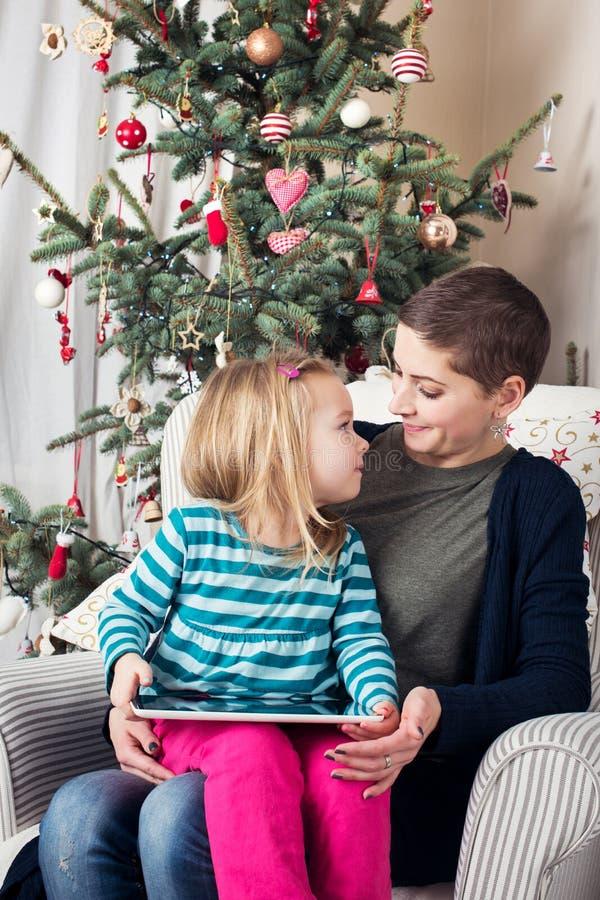 Menina pré-escolar bonito que mostra sua letra a Santa ao mum na tabuleta digital imagem de stock royalty free