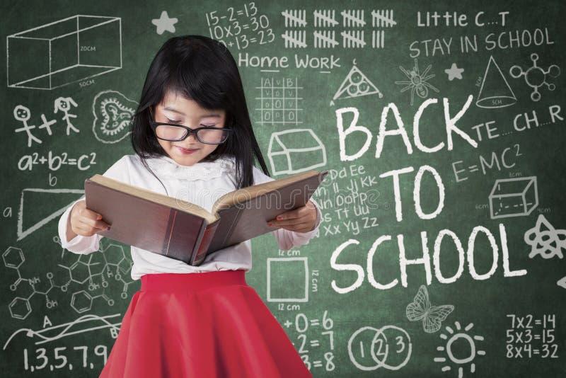 A menina pré-escolar lê o livro seriamente foto de stock
