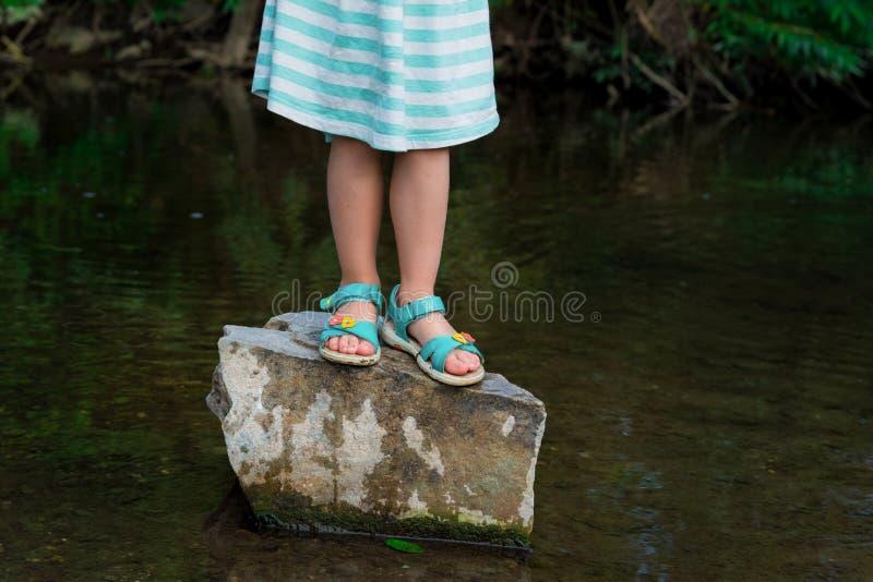 Menina pré-escolar loura adorável que joga no rio foto de stock