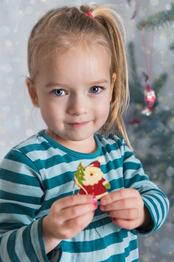 Menina pré-escolar loura bonito que decora a árvore de Natal Tempo autêntico do xmas da família fotos de stock