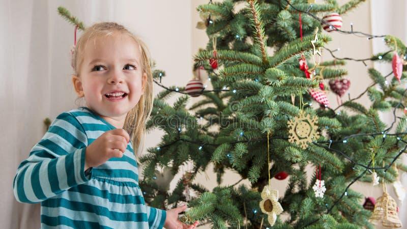 Menina pré-escolar loura bonito que decora a árvore de Natal Tempo autêntico do xmas da família foto de stock royalty free