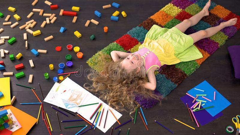 Menina pré-escolar loura encaracolado que encontra-se no tapete, sonhando e sorrindo, criança feliz imagens de stock royalty free