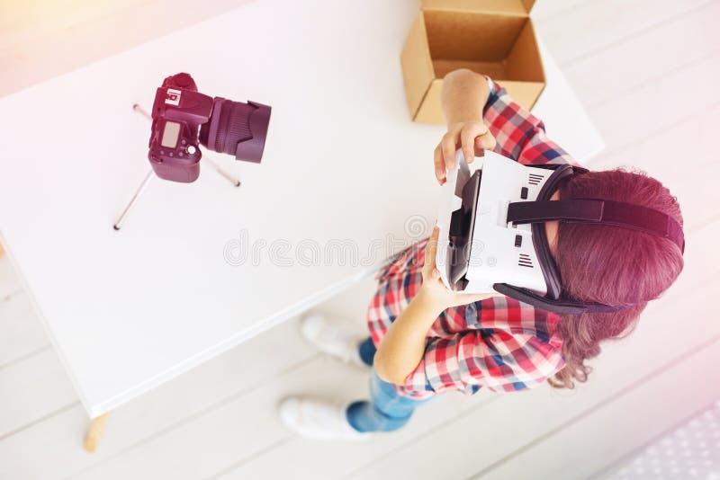 Menina pré-escolar moderna que é pouco blogger que filma o vídeo sobre vidros da realidade virtual fotos de stock royalty free
