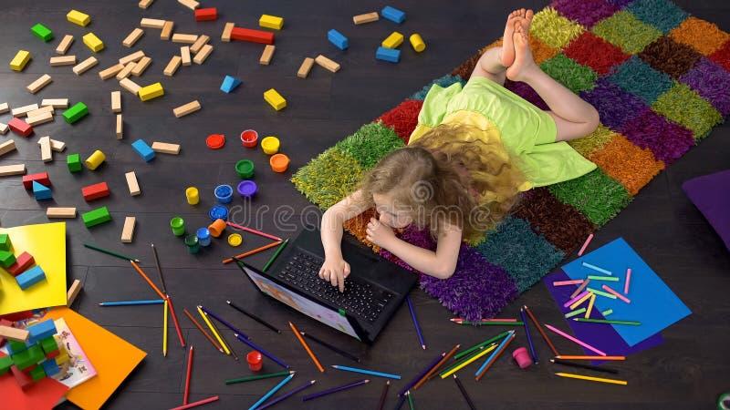 Menina pré-escolar que aprende letras no portátil, software educacional, infância fotos de stock