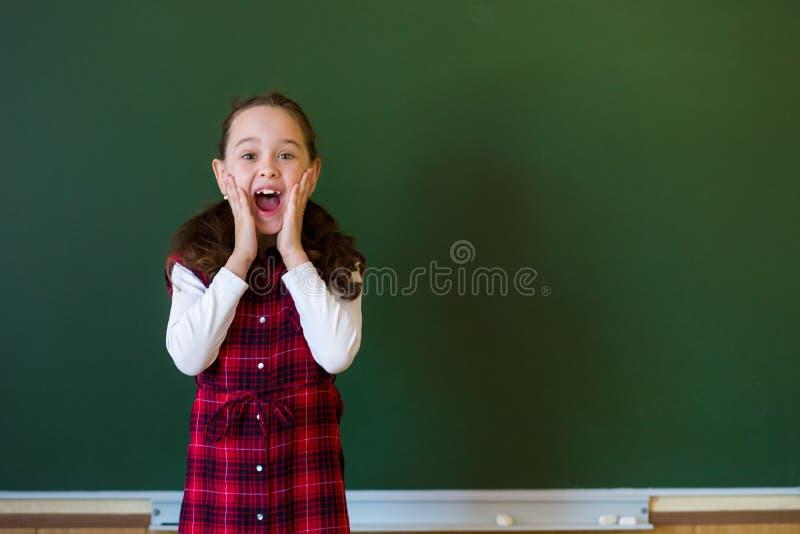 Menina pr?-escolar da estudante feliz na posi??o do vestido da manta na classe perto de um quadro-negro verde Conceito da educa?? imagens de stock royalty free