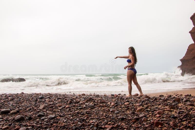 Menina, praia e mar no dia nebuloso imagens de stock royalty free