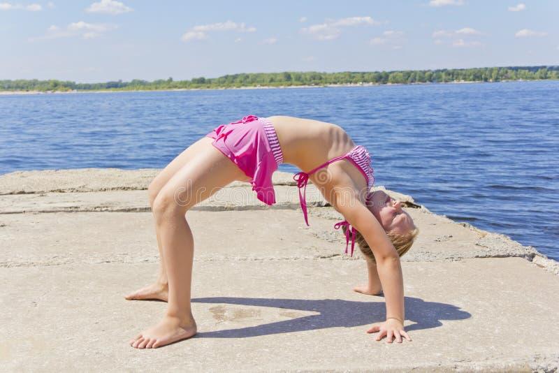 A menina pratica a ioga fotografia de stock