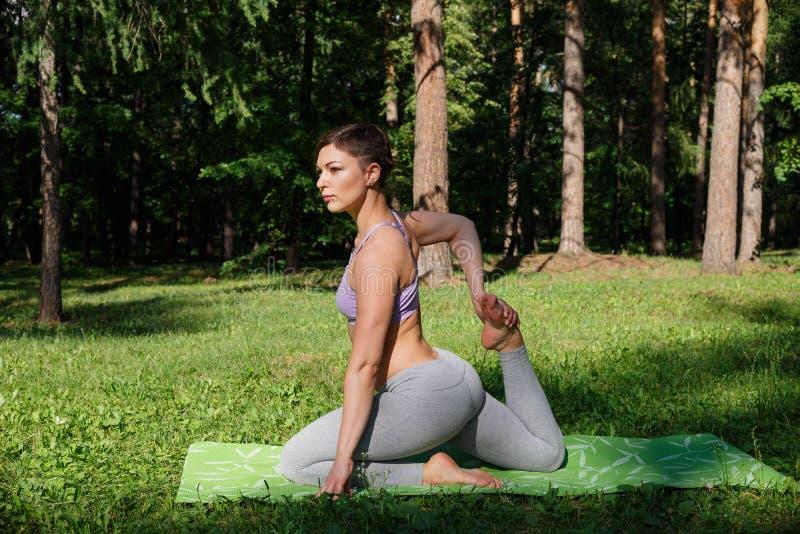 A menina pratica a ioga no parque em um dia ensolarado fotografia de stock royalty free