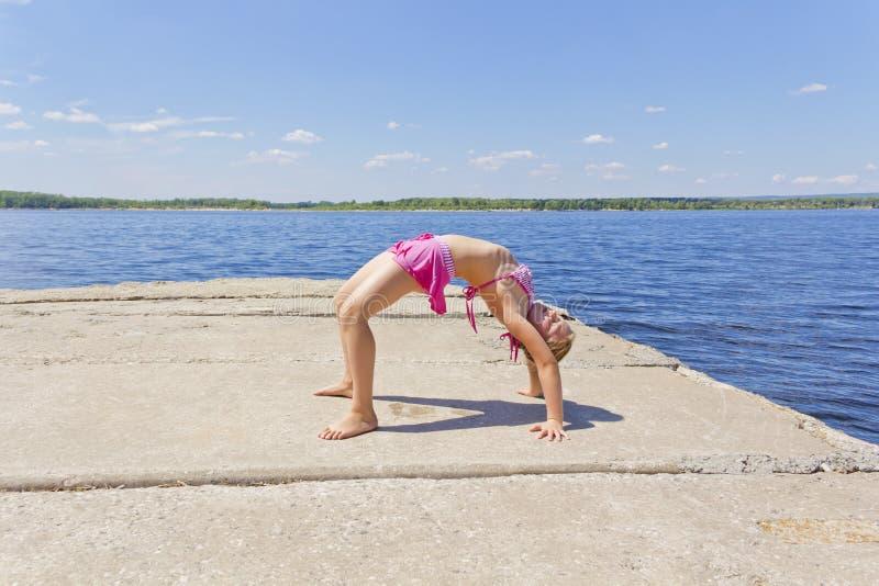 A menina pratica a ioga no passadiço da pose foto de stock royalty free