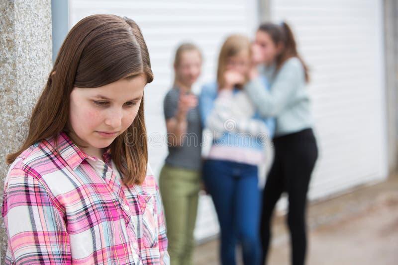 Menina pre adolescente triste que sente esquerda para fora por amigos imagens de stock