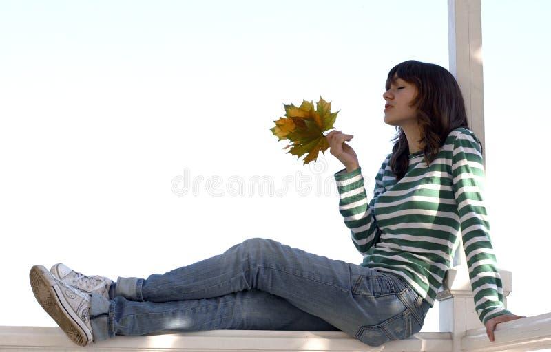 A menina prende as folhas do outono fotos de stock