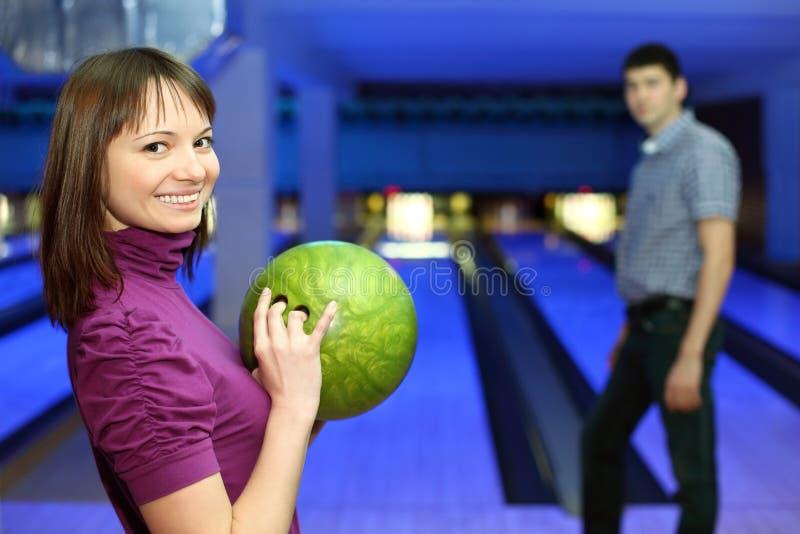 A menina prende a esfera para o bowling e o olhar do homem nele imagem de stock royalty free