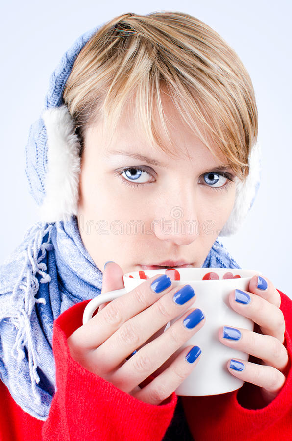 A menina prende o copo do chocolate quente. A imagem tem o clippin imagens de stock