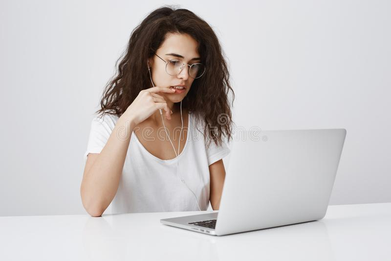 A menina preocupada encontrou o erro em seu projeto durante o trabalho no escritório Retrato da fêmea encaracolado-de cabelo conf imagens de stock royalty free