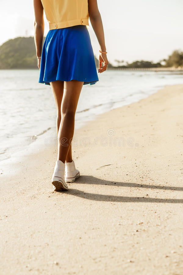 A menina preta adolescente bonita nas sapatilhas brancas na areia de seja imagens de stock