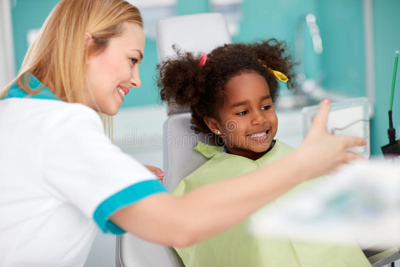 Menina preta agradável na cadeira dental que mostra os dentes no espelho ao denta imagem de stock royalty free