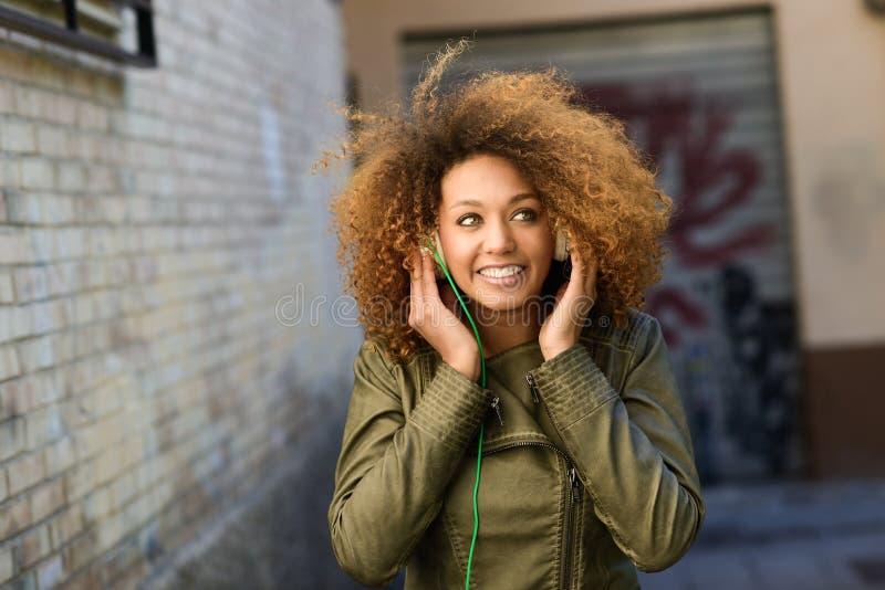 Menina preta atrativa nova no fundo urbano fotografia de stock