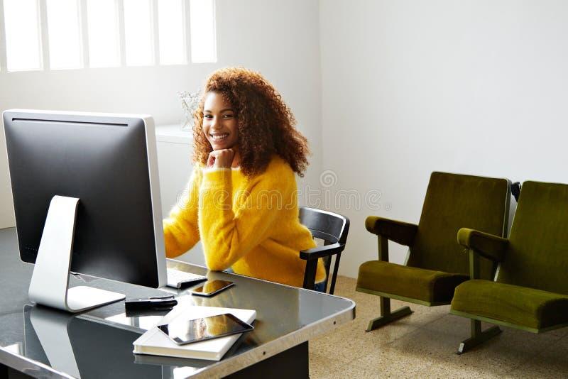 A menina preta bonita nova trabalha no escritório domiciliário fotografia de stock