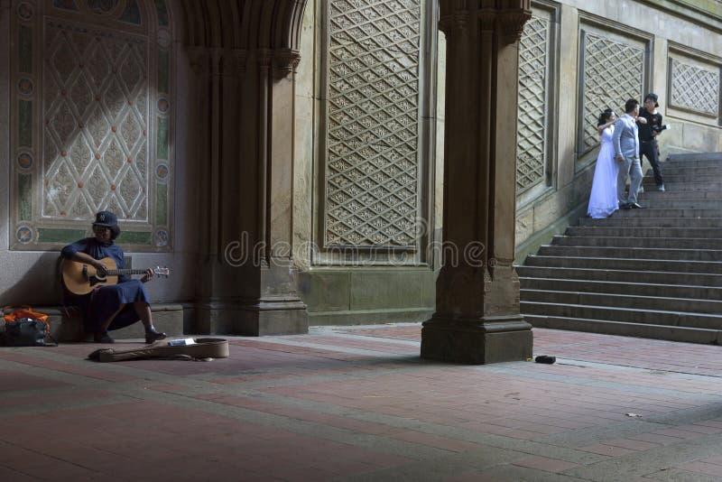 A menina preta canta e joga a guitarra sob a arcada de bethesda em y novo imagens de stock royalty free
