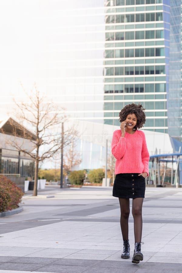 Menina preta com o telefone em torno da cidade imagens de stock