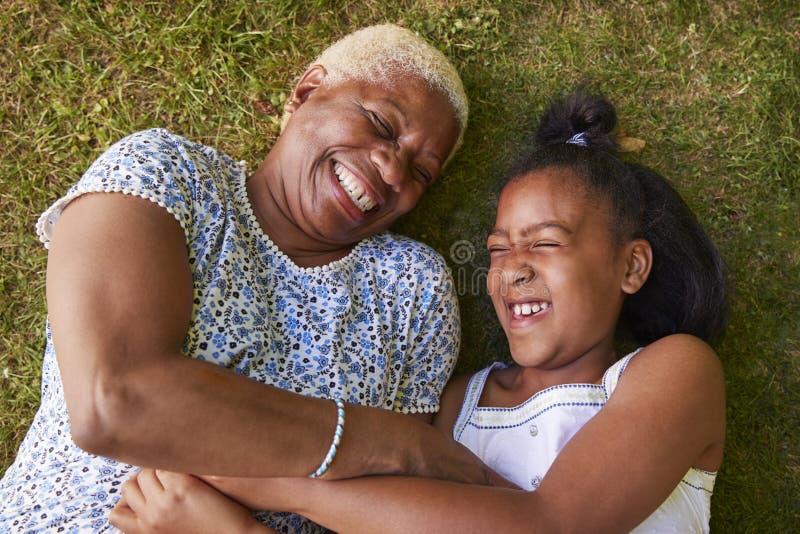 Menina preta e avó que encontram-se na grama, fim aéreo acima imagem de stock