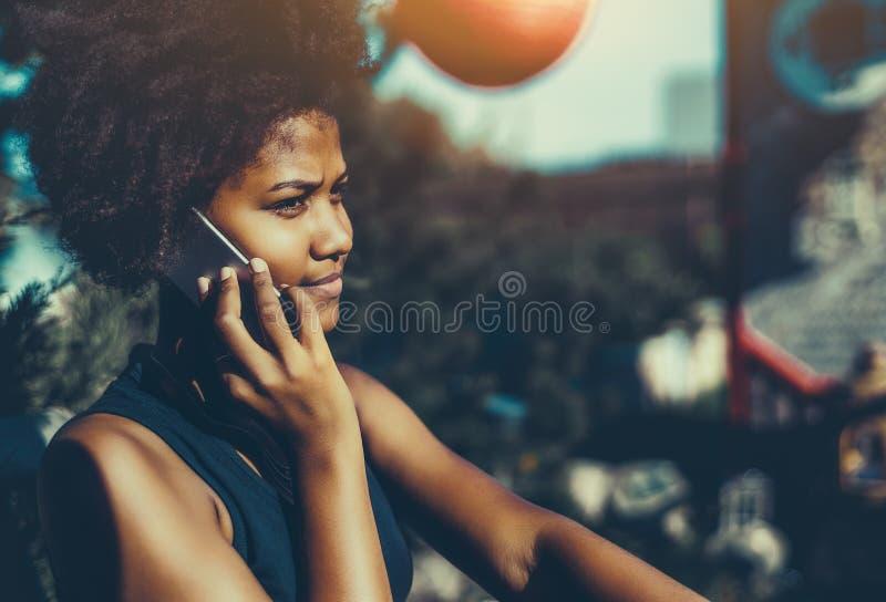 Menina preta encaracolado no parque que chama através do smartphone fotografia de stock royalty free