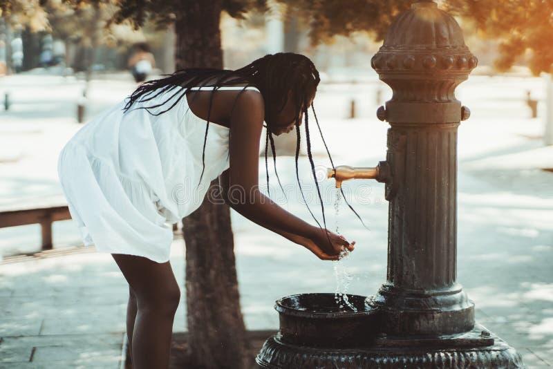 A menina preta está usando a bacia da rua imagens de stock royalty free