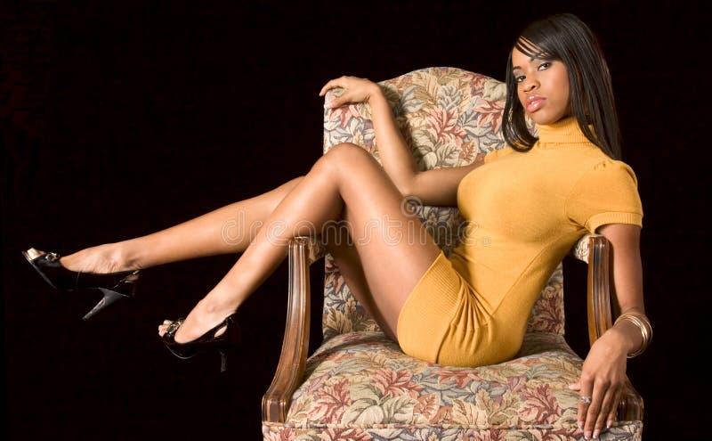 Menina preta glamoroso na cadeira fotos de stock