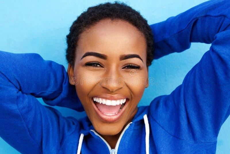 Menina preta nova bonita que ri com mãos atrás da cabeça fotografia de stock royalty free