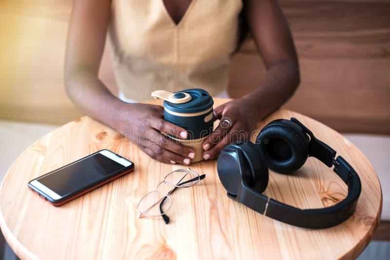 Menina preta nova que escuta a música no smartphone no café foto de stock