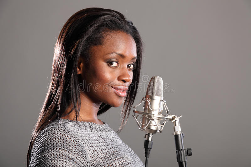 Menina preta nova que faz a música no estúdio de gravação imagem de stock