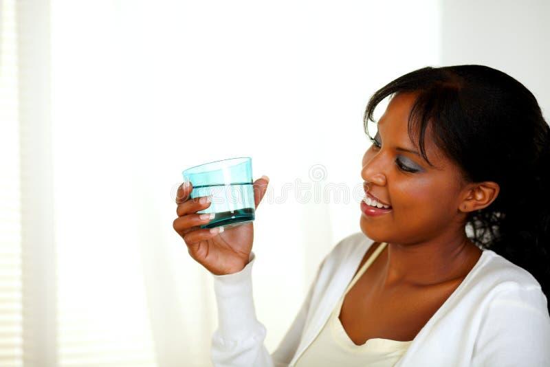 Menina preta nova que olha a um vidro de água fresca imagem de stock