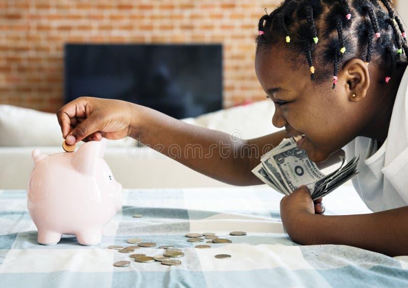 Menina preta que recolhe o dinheiro ao mealheiro imagem de stock