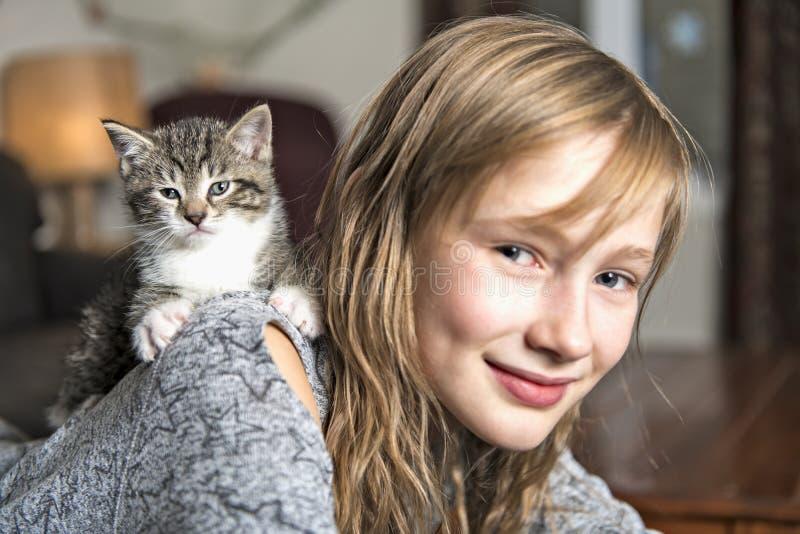 Menina Preteen de 10 anos velho com seu animal de estimação do gato no sofá fotografia de stock royalty free