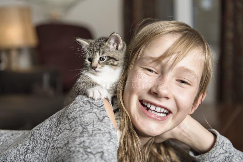 Menina Preteen de 10 anos velho com seu animal de estimação do gato no sofá imagens de stock royalty free