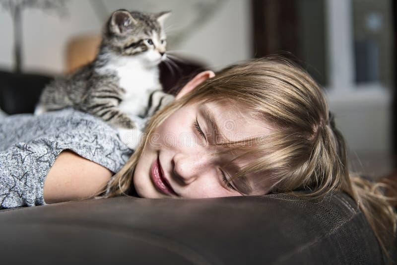 Menina Preteen de 10 anos velho com seu animal de estimação do gato no sofá foto de stock royalty free