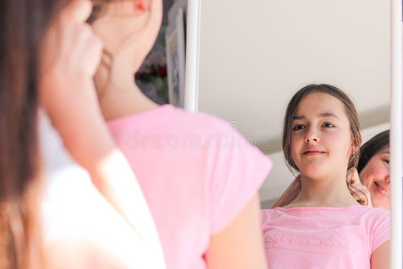 Menina preteen de sorriso bonita que olha sua reflexão no espelho quando sua mãe que faz o cabelo imagens de stock royalty free