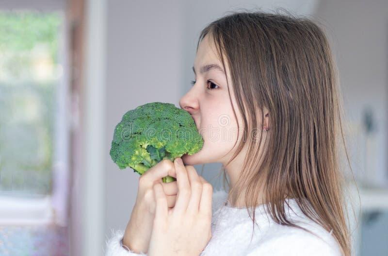 Menina preteen engraçada que morde e que come brócolis crus Dieta e conceito saudável do alimento, do vegetariano ou do vegetaria fotos de stock