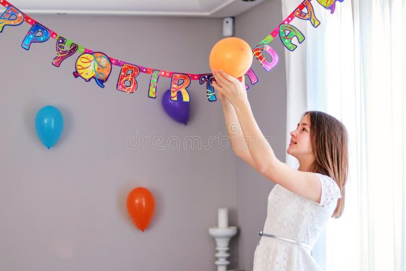 Menina preteen feliz que pendura acima dos balões que decoram a casa que prepara-se à festa de anos fotografia de stock royalty free
