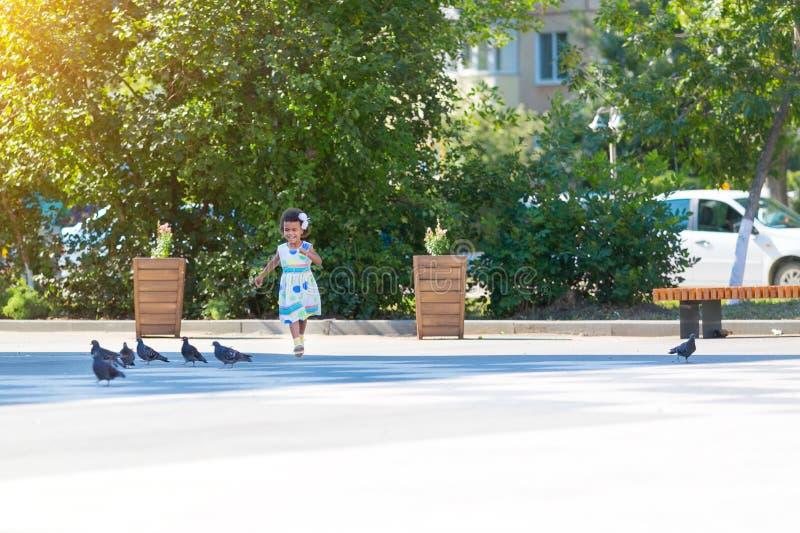 A menina preto-descascada está dançando atrás dos pombos imagens de stock