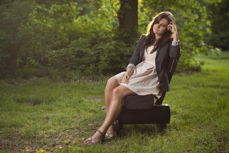 Menina profundamente nos pensamentos que sentam-se em um banco no parque imagem de stock royalty free