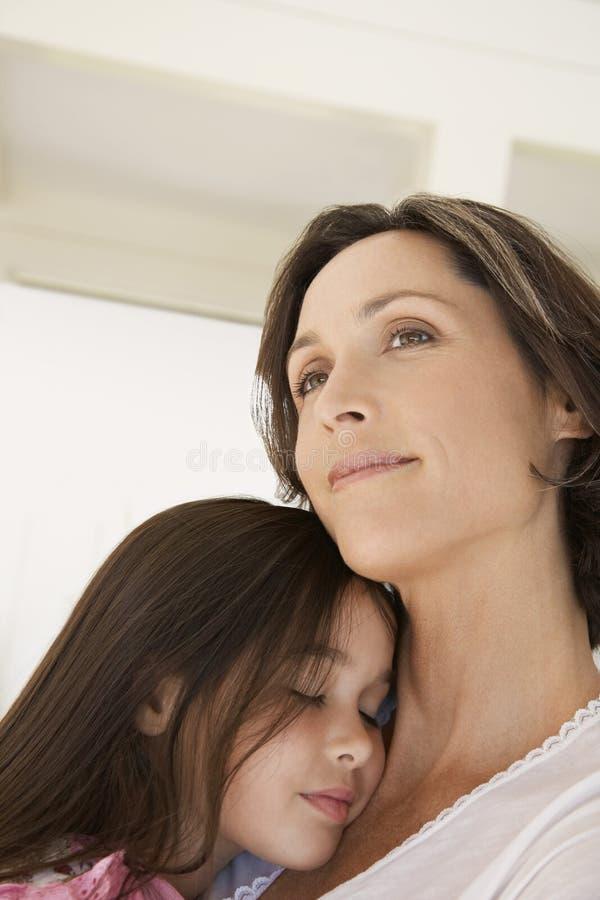 Menina que abraça a mãe em casa imagem de stock
