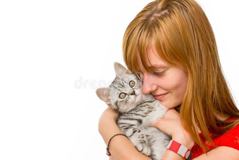 Menina que abraça o gato de gato malhado de prata novo imagem de stock royalty free